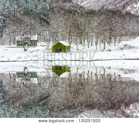 wooden houses on the banks of the Norwegian fjord with reflection in water