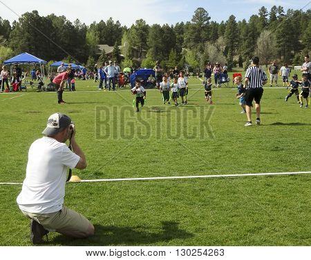 FLAGSTAFF, ARIZONA, MAY 14. Foxglenn Park on May 14, 2016, in Flagstaff, Arizona. A photographer shoots a flag football game at Foxglenn Park in Flagstaff Arizona.