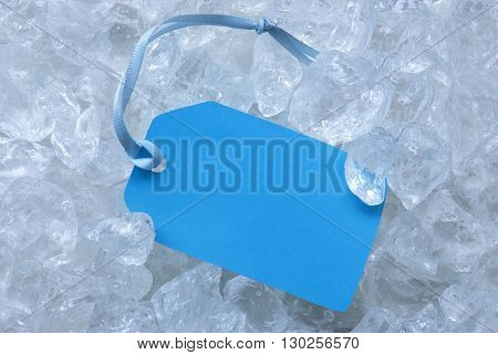 Light Blue Label With Blue Ribbon On White Transparent Curshed Ice Cubes As Background. Copy Space Or Free Text Or Your Text Here For Advertisement Or Cool Greetings.Close Up Or Macro View.