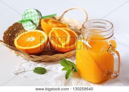 Orange juice in a glass mug and oranges