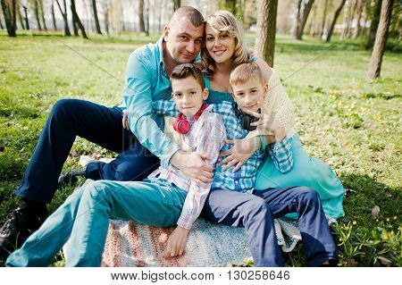 Happy Pregnant Family With Two Sons, Dressed In A Turquoise Clothes Sitting On Grass With Flowers At