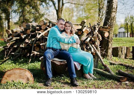 Happy Pregnant Family Dressed In A Turquoise Clothes Sitting On A Stump At Park