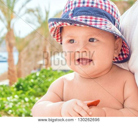 Portrait of a pretty baby with a hat outdoor shot