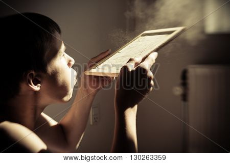 Boy Blowing Dust From Chalk Board