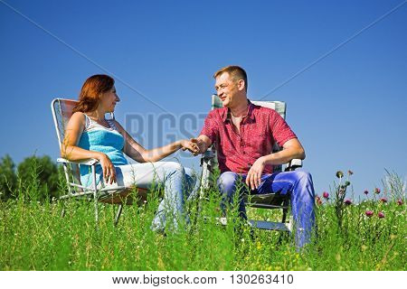Adult couple rest on the summer meadow