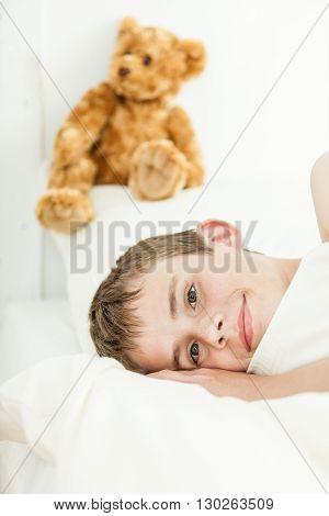 Smiling Boy Laying Down Near Plush Bear