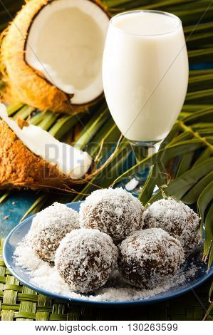 Coconut and chocolate rum balls and milk on green mat of palm leaves and half of coconut. Wooden blue background
