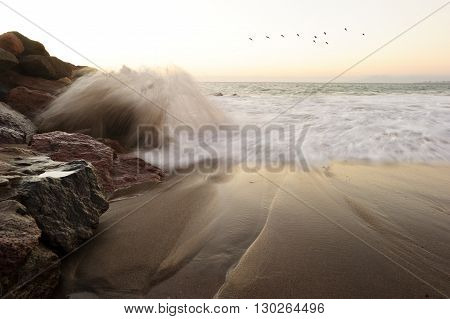Waves crashing is an ocean seascape with a wave crashing up against a rock throwing water into the air as birds fly in the background..