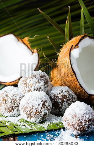 Coconut and chocolate rum balls on green mat of palm leaves and half of coconut. Wooden blue background