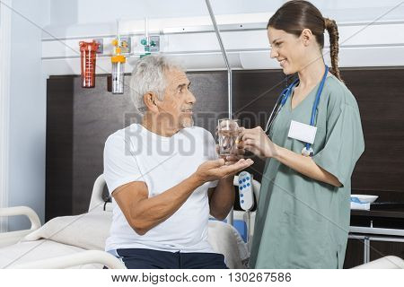 Patient Receiving Water Glass And Pill From Female Nurse
