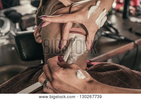 Female barber shaving a client's beard in a barber shop