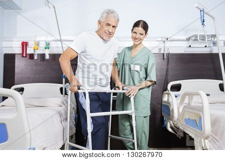 Nurse With Senior Man Using Walker In Rehab Center