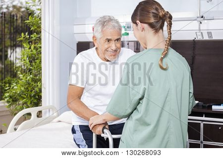 Senior Man Being Assisted By Female Nurse In Using Walker