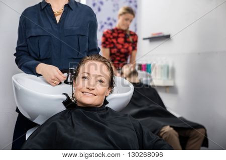 Happy Woman Getting Hair Washed In Salon