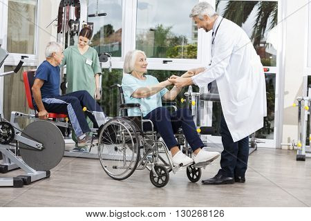 Doctor Holding Senior Woman's Hands In Wheelchair