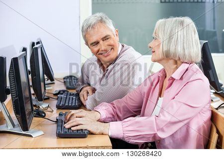 Happy Senior Students Communicating In Computer Class