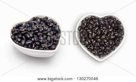 Black beans  in a heart shaped bowl, isolated on white