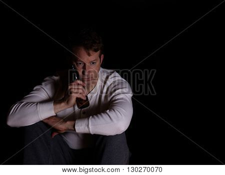 Depressed man holding bottle of beer against face while in thought. Dark background.