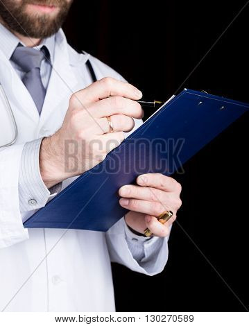 close-up hands of a doctor, he takes notes in a patient's medical history.