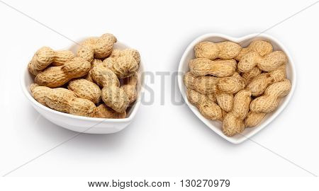peanuts in a heart shaped bowl, isolated on white