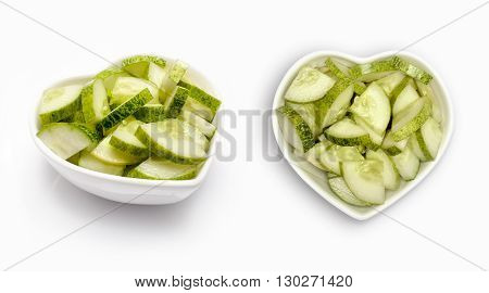 sliced cucumbers  in a heart shaped bowl, isolated on white