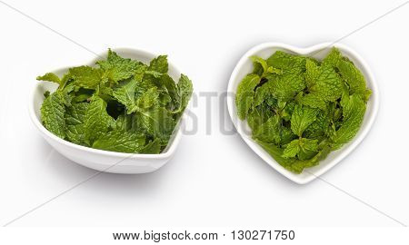 Fresh mint leaves  in a heart shaped bowl, isolated on white