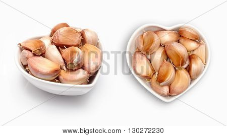 Fresh garlic   in a heart shaped bowl, isolated on white