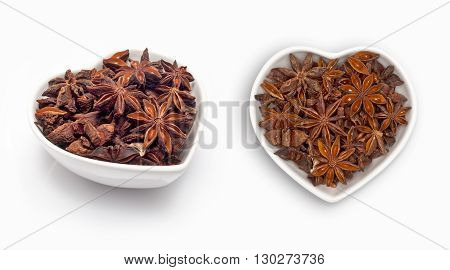 Star anise  in a heart shaped bowl, isolated on white
