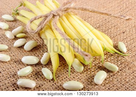 Heap of seeds and stack of beans tied with string lying on jute canvas healthy food and nutrition