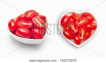 Olive tomato  in a heart shaped bowl, isolated on white