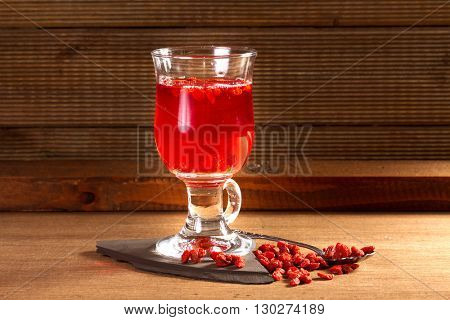 Glass healing infusion of goji berries and dried berries nearby.