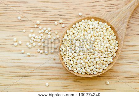 Raw Chenopodium quinoa in wooden spoon on wooden background.