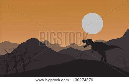 Silhouette of one tyrannosaurus in hills with sun at afternoon