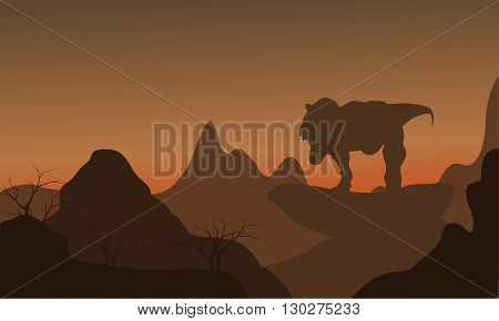 Silhouette of tyrannosaurus standing in rock at the afternoon