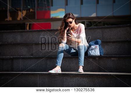 young woman student take break at stairs outdoor at city use smartphone