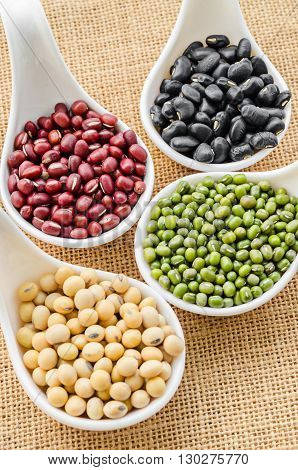 Set of beans Mung bean Soy or yellow bean Azuki or red bean and black bean in white spoon on sack background.