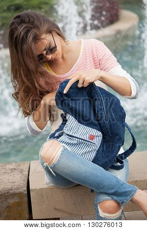 young woman in casual clothes, jeans, t-shirt and sunglasses take a break by city fountain