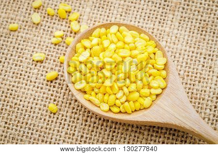 Peeled split mung bean in wooden spoon on sack background