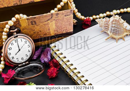Open diary and vintage pocket watch with decorate on black background.