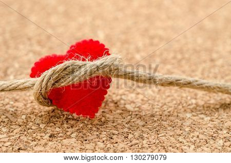 Red heart with a bundle rope on wooden board