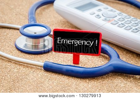 Phone and stethoscope on the table with EMERGENCY HOTLINE words on the board. Medical concept.