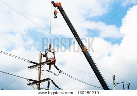 The technician works in a bucket high up on a power pole