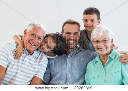 Portrait of happy family sitting on sofa and smiling in living room