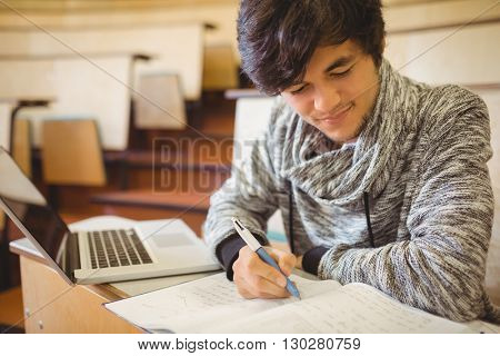 Young student sitting at a desk writing notes in the classroom