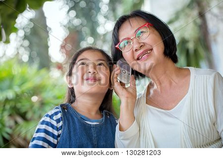 Little Asian girl calling mobile phone with her grandmother
