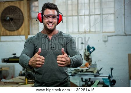Carpenter is posing with his thumbs up and his protection equipment in a dusty workshop