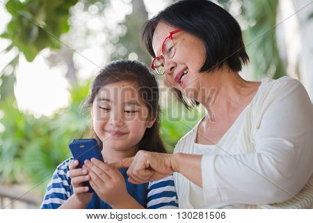 Little Asian girl using mobile phone with her grandmother