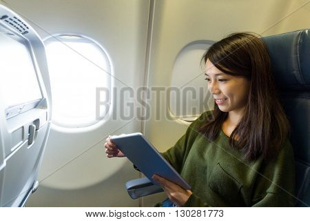 Woman use of digital tablet pc inside aircraft