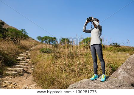 Hiker looking in binoculars enjoying spectacular view on mountain