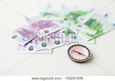 business, economy, finance and investment concept - close up of compass and euro money on table